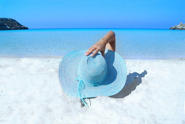 a woman with blue hat is sunbathing