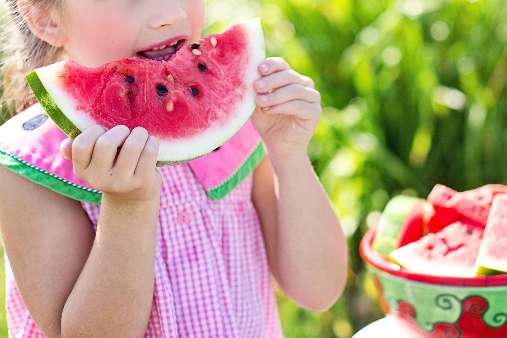 a kid eating watermelon